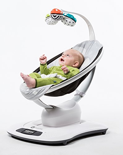 laughing baby lying in mamaroo playing with mobile